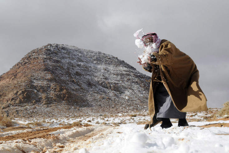 A man plays with snow after a snowstorm in the desert, near Tabuk